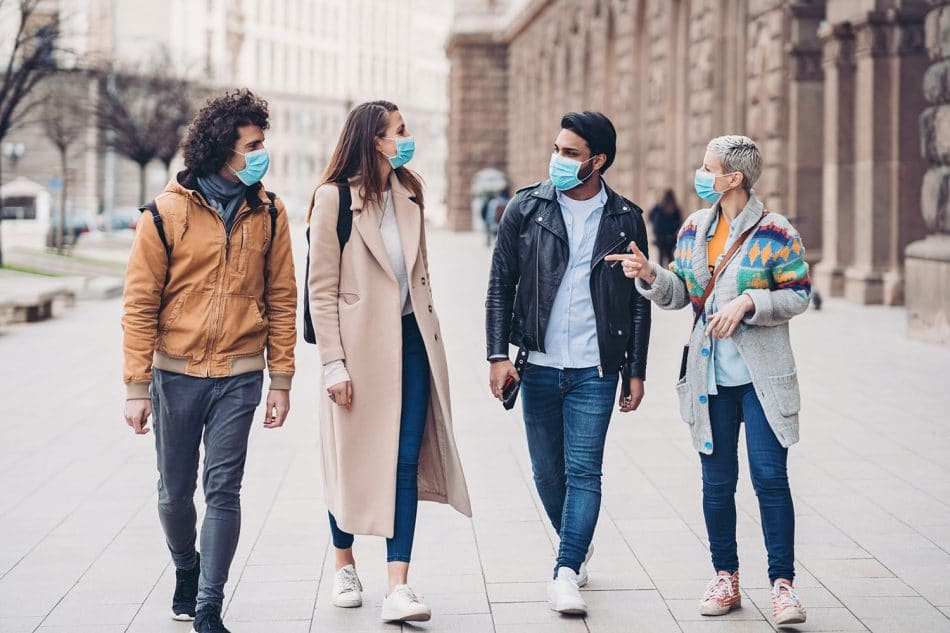 4 friends walk down the street each wearing PPE masks