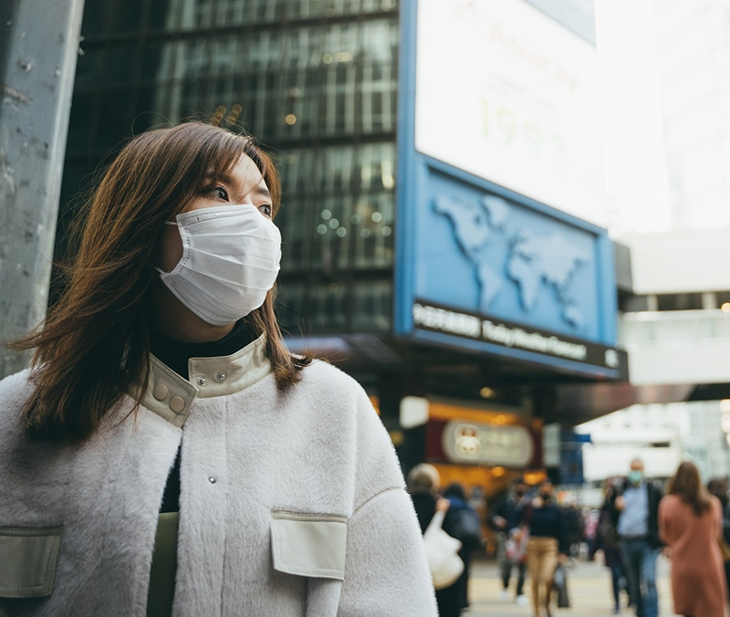 an asian woman in a city wears a facemask outside